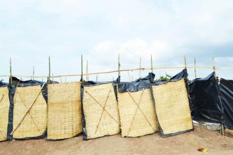 Bamboo mats lined with tarpaulin as toilet partitions.