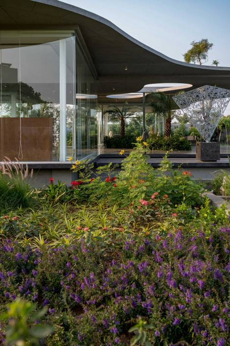 Office in the garden: A border of flowering plants, landscape elements and contemporary art work with the open & transparent layout of the office: a new vocabulary for offices in India.